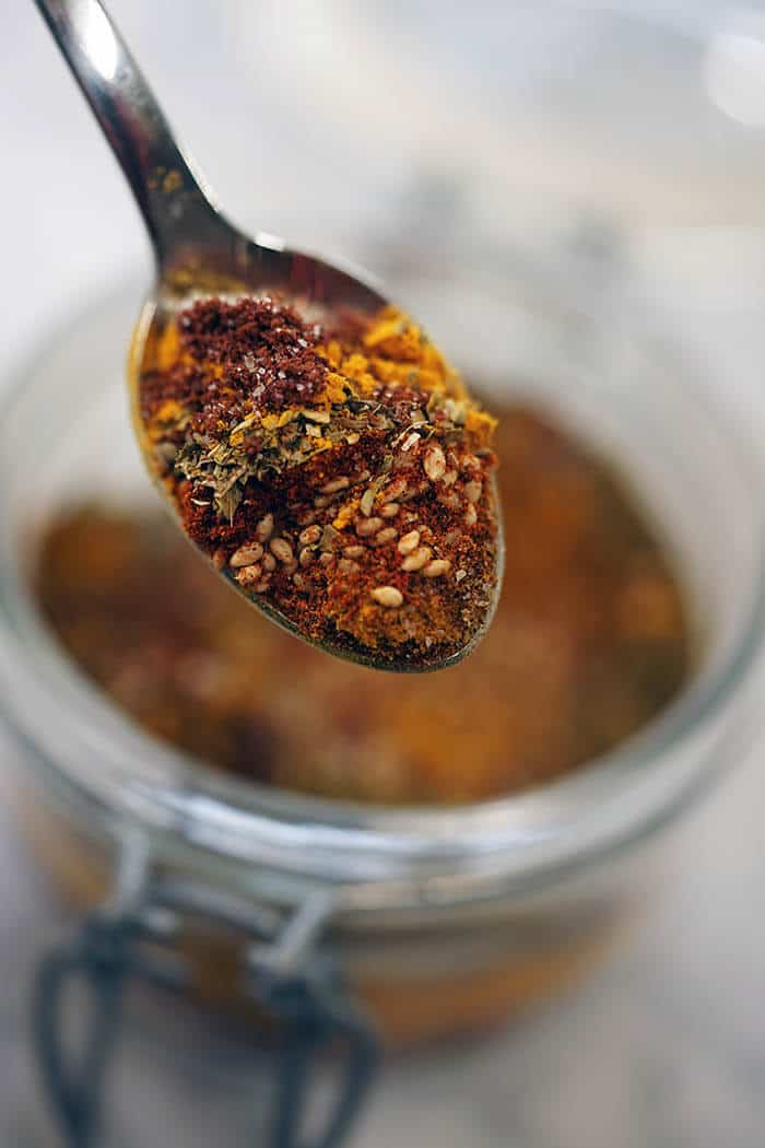 A spoon filled with spice mix.