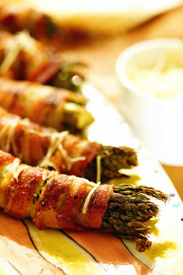 Grilled Bacon Wrapped Asparagus on a colorful platter with a bowl of parmesan cheese for sprinkling on top.